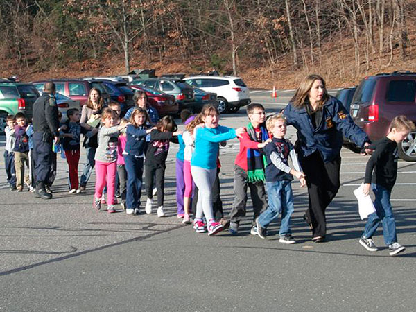 State police personnel lead children to safety away from the Sandy