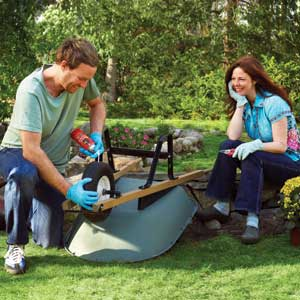man lubricating wheelbarrow while woman with pruners looks on