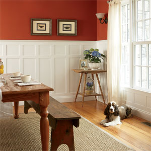 dog sitting on floor in wainscoting paneled rustic room red dining room