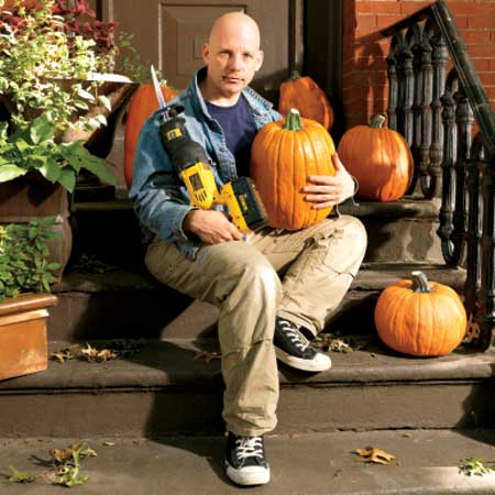 This Old House Editor, Scott Omelianuk with a reciprocating saw and some pumpkins sitting outside his front stoop