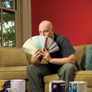 TOH Editor, Scott Omelianuk in a room with paint cans and a fan of swatches in front of his face