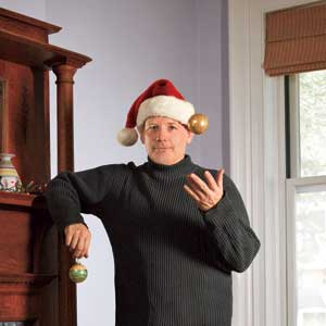 This Old House Editor, Scott Omelianuk with a Santa hat, x-mas ornaments and leaning on the mantel