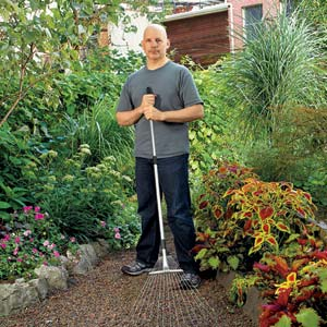 This Old House editor, Scott Omelianuk standing in a gravel walkway through a garden holding a rake
