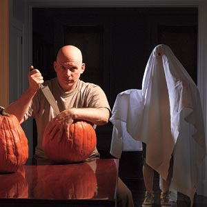 TOH editor, Scott Omelianuk carves a pumpkin with person wrapped in sheet behind him