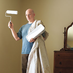 TOH editor, Scott Omelianuk draped in a drop cloth holding a paint roller and tray