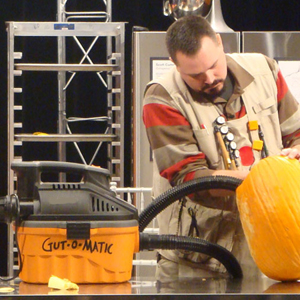 Scott Cummins uses his shop vac to gut a pumpkin for carving