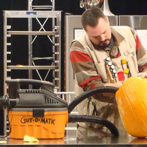 Scott Cummins uses his shop vac to gut a pumpkin for carving