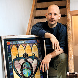Scott Omelianuk on a stairway leaning on a salvaged stained glass window