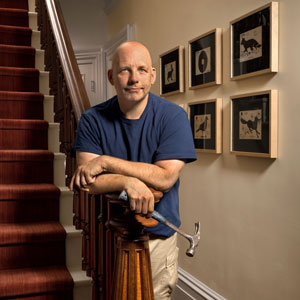 Scott Omelianuk leans on a baluster with framed artwork behind him, a new acquisition is inset at bottom right