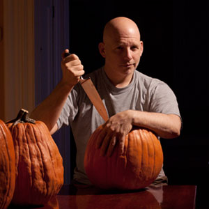 TOH Editor Scott Omelianuk holding a knife over a pumpkin as a ghost looks on from behind him for the letter from the editor, On the Great TOH Pumking Carving Contest: Who's the Scariest of All?