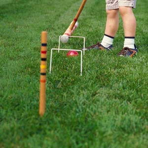 child playing croquet on lush, healthy lawn