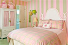 a whimsical headboard painted onto a wall boldly painted with wide pink and green stripes with color matched furniture including a bed with bedspread and pillows, a hutch, lamps, and other miscellaneous bedroom furniture