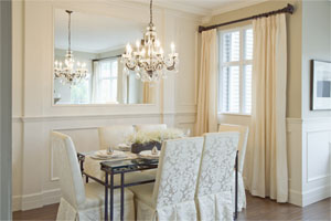 clean, well-lit formal dining room in cream colors with a lit chandelier hanging over the fully-set table, with a mirror set into the wall behind the table, above the wainscotting