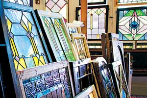 a collection of brightly colored and patterned stained glass windows stacked together in a salvage warehouse, with more examples of stained glass windows hanging in the background