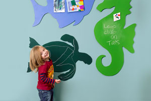 a child looks out at the camera smiling, holding a piece of chalk. Behind them on the wall are three, large, colorful, animal-shaped drawing surfaces. There is a fish, a seahorse and a turtle.