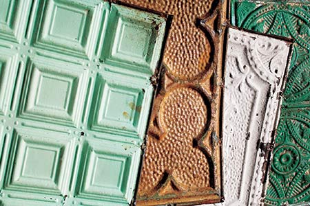four vintage embossed salvage tin ceiling tiles overlapping, including a kelly green one, a white one, a rust one, and a mint colored one