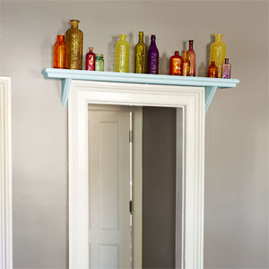 a shelf mantel with a row of colorful antique glass bottles installed over a door. another door is visible through the open door.