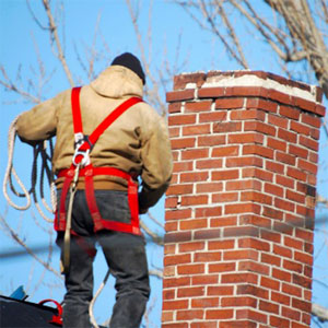 a person with their back facing the viewer standing on a rooftop next to a brick chimney-top. the person wears a coat and a harness