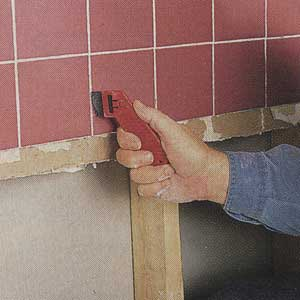 Scratching out existing grout from between ceramic tiles with a grout saw.