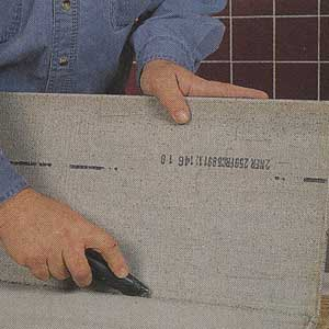slicing the fiberglass mesh of the cement backerboard