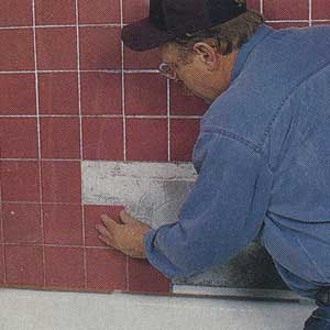 pressing shower tiles into the mastic