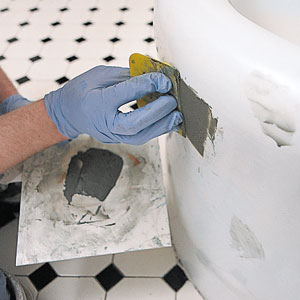 filling dings and scratches of an old tub with putty before shining