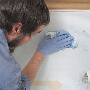 applying a blue bonding agent over the tub's surface before refinishing
