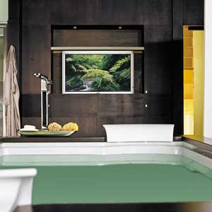 Flat screen TV hanging on the wall over a bathtub
