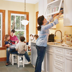 mother looking in cabinet while family is in background of kitchen