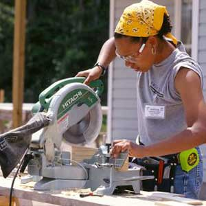 woman using table saw on Habitat for Humanity Women Build site