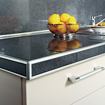 a granite tile countertop with protective metal edges