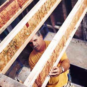 Tom Silva tightening i-joists before installing a floor