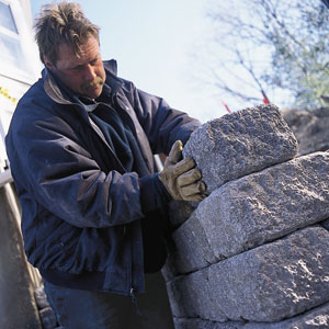 Roger Cook inspects a cobblestone retaining wall