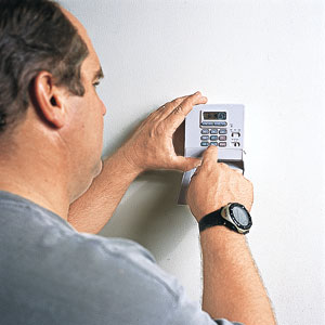Richard Trethewey adjusts a programmable thermostat