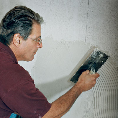 tiling contractor Mark Ferrante spreads thinset with a square-notched trowel