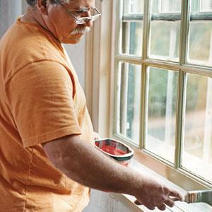 John Dee paints the inside of a window