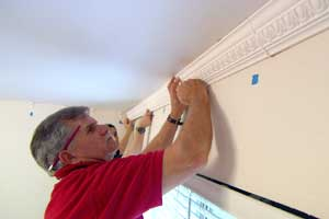 man reaching up to install crown molding