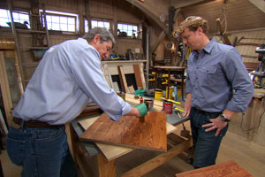 two people in a workshop with one watching the other apply finish to a piece of wood with a paintbrush