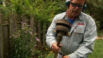 a man wearing safety goggles inspecting the bottom end of a string trimmer