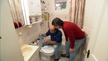 two people installing a new dual flush feature to a toilet bowl