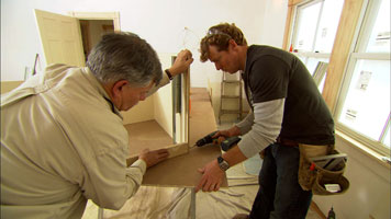 two people attaching two pieces of wood using a drill driver