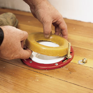 installing a new wax ring over a closet flange to seal up a toilet bowl