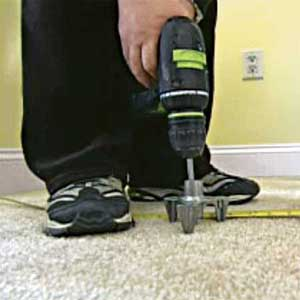 man drives a snap-off screw into carpeted subfloor