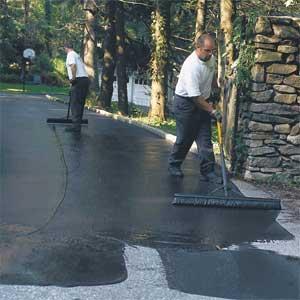 men applying sealant to an asphalt driveway