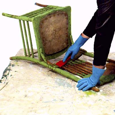 person scraping old paint off of a vintage chair