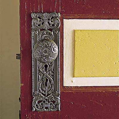 century-old brass doorknob and red, yellow, and cream paint on Queen Anne door