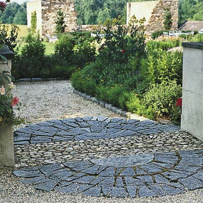 pea gravel underfoot leads to an oval of decorative hardscape of granite semicircles flanked by short stucco pillars
