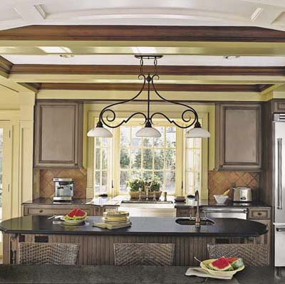 A kitchen with production moldings, a pendant light, a coffered ceiling, and a island