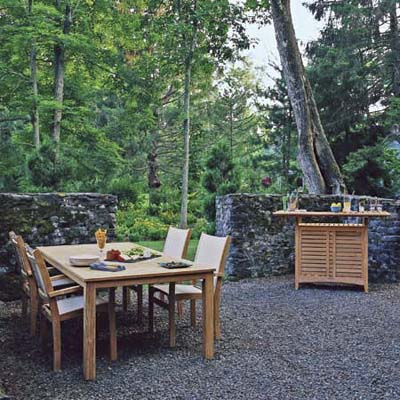 outdoor dining area on gravel bedding, surrounded by woods and rock wall for privacy