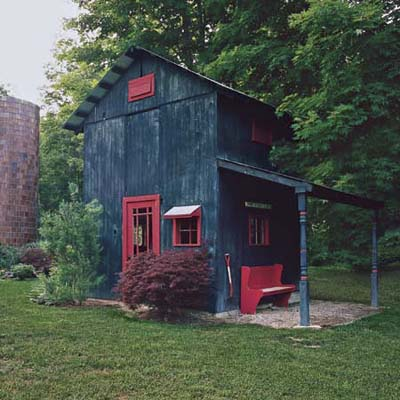 outbuilding with dark blue vertical plank siding, bright red trim, door and bench with a red-handled pitch fork to accessorize